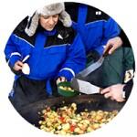 Bild på människor som lagar mat utomhus.