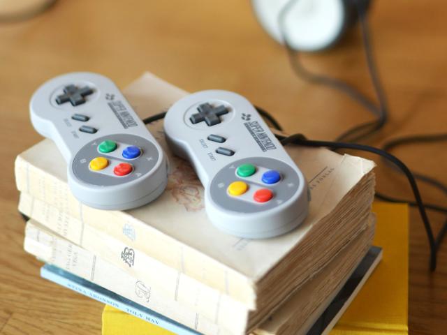 Två Super Nintendo-kontroller ligger på en trave böcker.