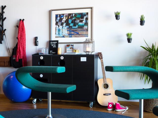 Vy över Kreativa konferensrummet och dess möblering. På bilden syns bland annat snurrstolar, en gitarr och en pilatesboll.