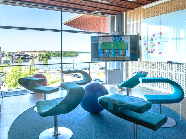 Vy över Kreativa konferensrummet och utsikten mot Norra hamn. På bildens syns snurrstolar, pilatesbollar, en TV med spelet Super Mario och en whiteboard med Post-it-lappar.