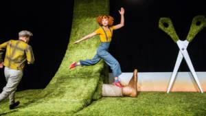 En kvinna som hoppar i gräset som rullats ut på scenen.
