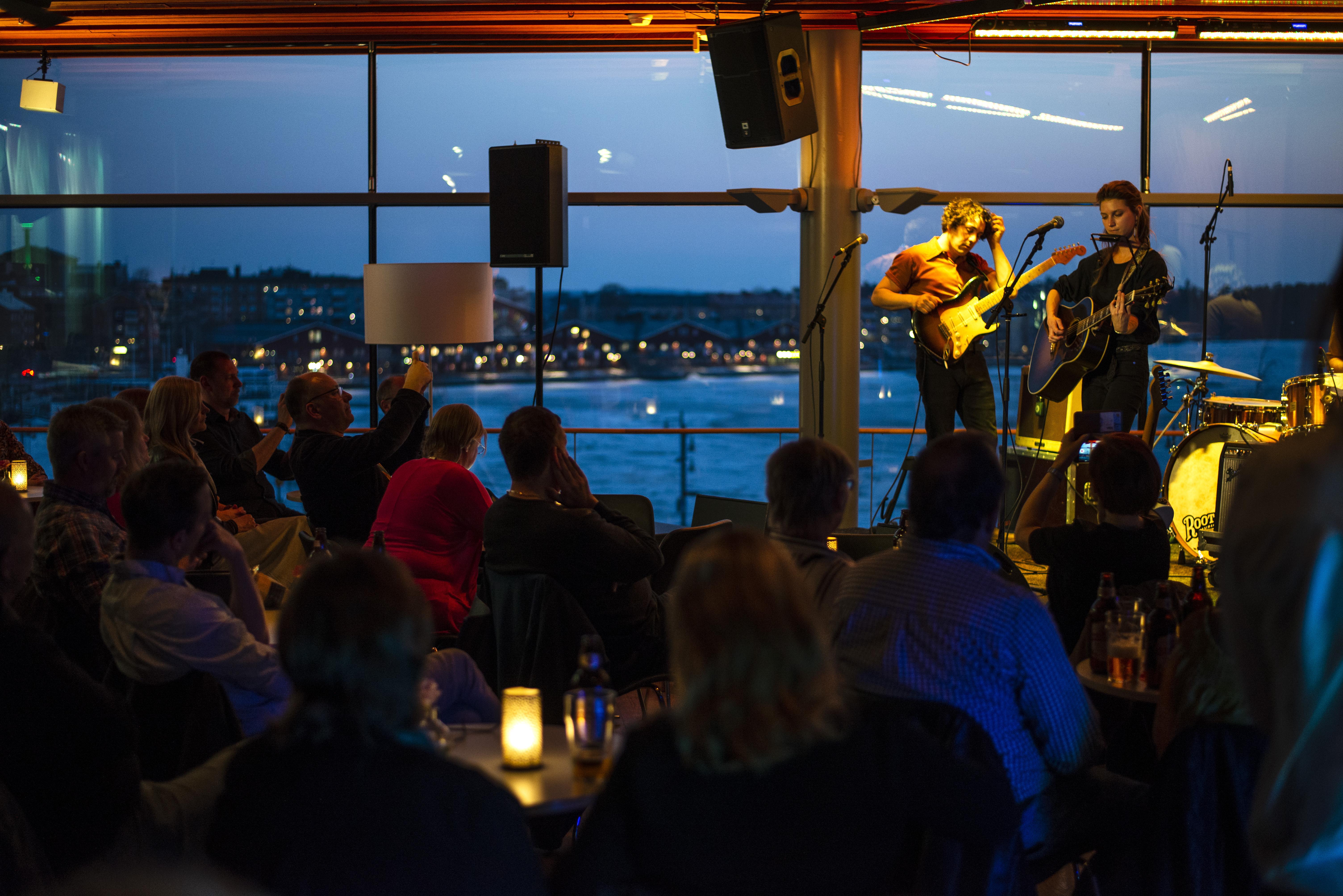 En konsert i barlokal med dunkelt ljus och utsikt över Luleås norra hamn.