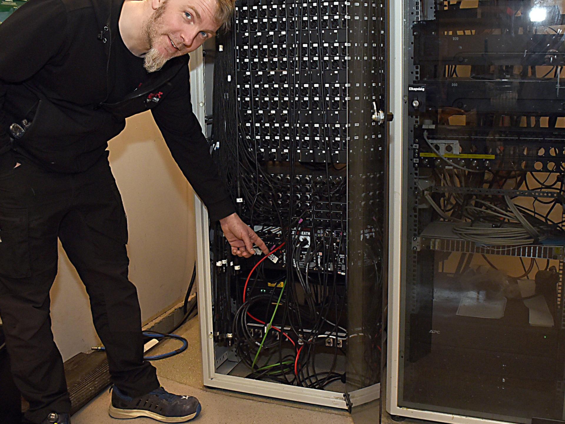 """Kaj Molin visar hur det ser ut backstage, när Stora salen fått ett nytt ljudsystem. """"Vi har dragit enorma mängder kablar"""", säger han."""
